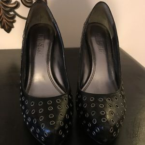 Black pumps with silver grommets.